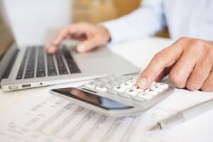 Male hand laptop computer calculator money pen